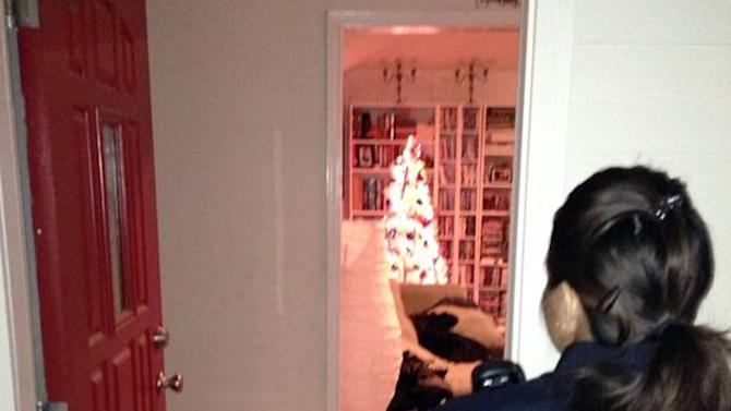 In this Dec. 14 photo provided by the Arlington, S.D., Police Department Officer Zhivonni McDonnell entering a home during a Tweetalong in Arlington, S.D. On a virtual ridealongs on Twitter, or Tweetalongs, officers post regular updates to Twitter about what they are seeing as they perform their normal on-duty routine. The tweets, which also include photos and links to videos of the officers, can encompass an array of activities. (AP Photo/Arlington Police Department)