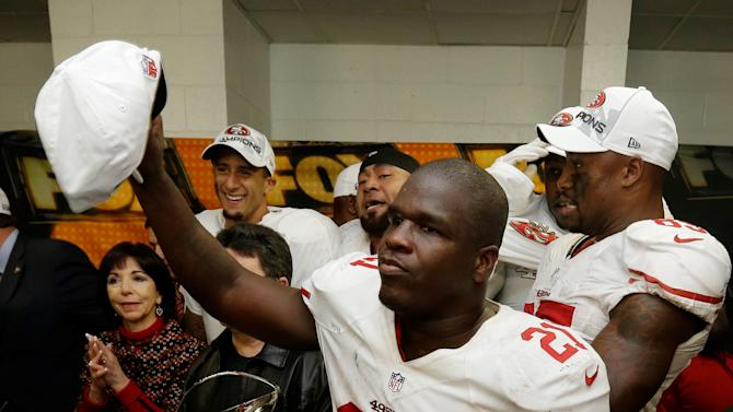 San Francisco 49ers' Frank Gore holds up a championship hat during the George Halas Trophy presentation after the NFL football NFC Championship game against the Atlanta Falcons Sunday, Jan. 20, 2013, in Atlanta. The 49ers won 28-24 to advance to Super Bowl XLVII. (AP Photo/Dave Martin)