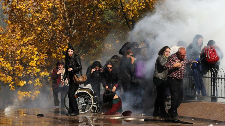 Protesters help a handicapped protester, who fell from her wheelchair after tear gas was shot towards them, in Ankara