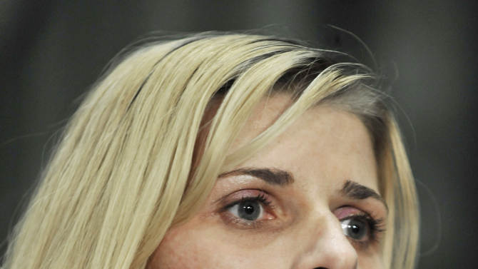 FILE - In this Nov. 13, 2012 file photo, bartender Karolina Obrycka, who was beaten in February 2007 by off-duty Chicago police officer Anthony Abbate, listens while her attorney Terry Ekl speaks during a news conference in Chicago after jurors awarded her $850,000 in damages. The city of Chicago and Obrycka, whose videotaped beating by Abbate drew national attention, have taken the unusual step of asking a judge to toss a landmark civil verdict in the case. In deciding against the city last month, jurors determined some officers follow a code of silence protecting rogue colleagues like the officer involved. If the judge grants the motion, the city would forgo any appeal and pay Obrycka the full damages immediately. Otherwise, a payment could be delayed years. Striking the verdict would deny others suing the city the chance to cite it as precedent. (AP Photo/Paul Beaty, File)