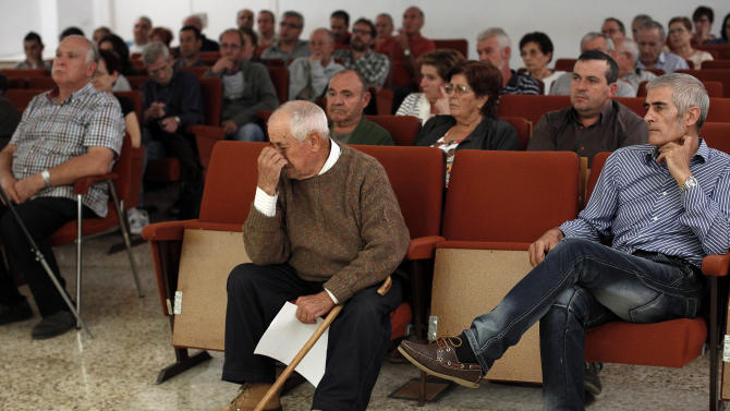 In this photo taken Oct 23, 2012, a man, a bearer of stock shares from Bankia, cries during during a meeting of the ApacBank association, which represents hundreds of Bankia clients who have had their money frozen,  in La Vall D'Uixo, near Valencia, Spain. Thousands of townspeople and nearly a million across Spain followed bank manager's advice and invested their life savings in the bank's stocks. Lured by the family-like ties nurtured between bankers and customers, they poured their life's savings into higher-yielding financial instruments recommended by the people managing their money. When boom turned to catastrophic bust, they found the stock they had acquired had become all but worthless. (AP Photo/Alberto Saiz)