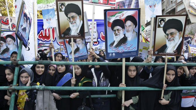 Holding posters of the late revolutionary founder Ayatollah Khomeini, and Supreme Leader Ayatollah Ali Khamenei, Iranian girls attend an annual state-backed rally in front of the former US Embassy in Tehran, Iran, Friday, Nov. 2, 2012. The rally marks the Nov. 4, 1979, storming of the building by militant students who held 52 Americans hostage for 444 days to protest U.S. failure to hand over the toppled shah Mohammad Reza Pahlavi to Iran for trial. Gen. Mohammad Reza Naqdi of the powerful Revolutionary Guard, not shown, addressed the rally saying the U.S. must annul the CIA, pull out its warships from the Persian Gulf and dismantle its military bases from 50 countries around the world if it wants to restore ties with Tehran. (AP Photo/Vahid Salemi)
