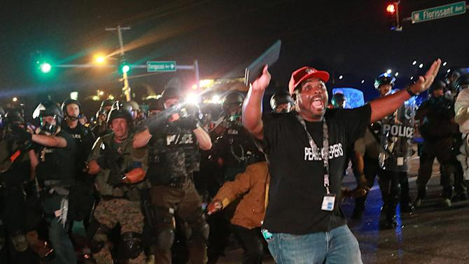 A citizen peacekeeper tries to keep protesters back as police advance Monday, Aug. 18, 2014, in Ferguson, Mo. The Aug. 9 shooting of Michael Brown by a police officer has touched off rancorous protests in Ferguson, a St. Louis suburb where police have used riot gear and tear gas. (AP Photo/St. Louis Post-Dispatch, Christian Gooden)