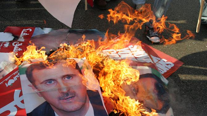 FILE - In this Thursday, Nov. 23, 2006 file photo, posters of Syrian President Bashar Assad are burned by anti-Syrian protesters during the funeral of assassinated Christian politician Pierre Gemayel, at the Martyrs square, in Beirut, Lebanon. Syria has a long and tumultuous history of meddling into Lebanese affairs. For much of the past 30 years, the seven-times-smaller Lebanon has lived under Syrian military and political domination. Since the uprising against President Bashar Assad began in February 2011, Lebanon has been steadily drawn into the unrest — a troubling sign for the country with political parties rooted in various Christian and Muslim sects, many of which are armed. (AP Photo/Hussein Malla, file)