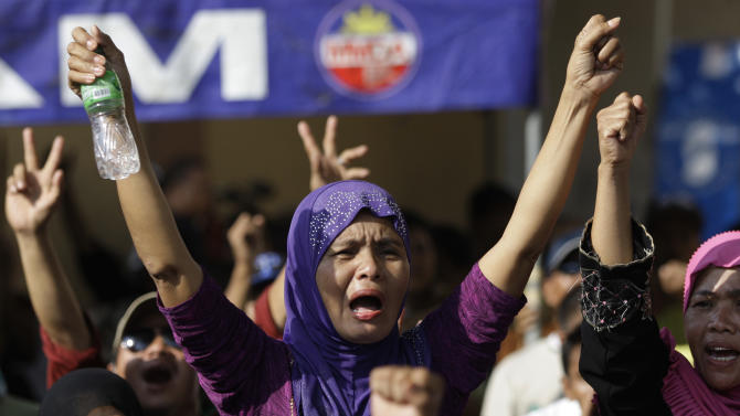 Filipino Muslim women celebrate after hearing news of the signing of a preliminary peace pact between the government and the nation's largest Muslim rebel group during a rally outside the gates of the Malacanang presidential palace in Manila, Philippines, on Monday Oct. 15, 2012. Muslim rebels and the Philippine government overcame decades of bitter hostilities and took their first tentative step toward ending one of Asia's longest-running insurgencies with the ceremonial signing of a preliminary peace pact Monday that both sides said presented both a hope and a challenge. (AP Photo/Aaron Favila)