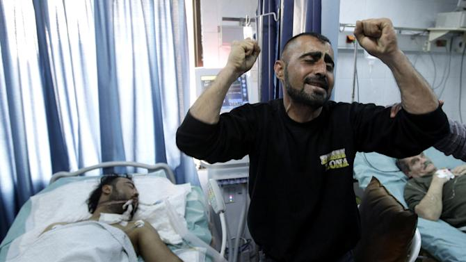 FILE - A Syrian man reacts next to his brother, who was seriously wounded during a violence between security forces and armed groups in Latakia, northwest of Damascus, Syria, on Sunday, March 27, 2011. (AP Photo/Hussein Malla, File)