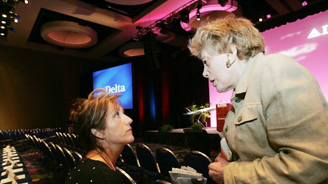 """FILE - In this Thursday, May 19, 2005 file photo, shareholder activist Evelyn Y. Davis, right, talks with a Delta associate who did not want to be identified at the Georgia International Convention Center, the site of the Delta Air Lines shareholders meeting, in College Park, Ga. For decades, Davis, who has been buying a few shares of big companies, attends their annual meetings, turning them into her personal stage. But in 2012, Davis didn't show up at any company's annual meeting. Age has finally made her do what the most powerful CEOs in America couldn't: Give it a rest. """"I'm not so young anymore,"""" said Mrs. Davis, 82. (AP Photo/Ric Feld)"""