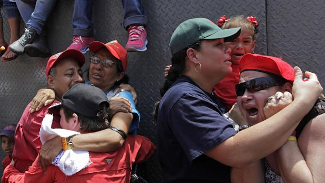 Supporters of Venezuela's late President Hugo Chavez embrace as the coffin containing his body passes in the street as it is taken from the hospital, where he died on Tuesday, to a military academy where his body will lie in state until his funeral in Caracas, Venezuela, Wednesday, March 6, 2013. Seven days of mourning were declared, all schools were suspended for the week and friendly heads of state were expected for an elaborate funeral Friday. (AP Photo/Rodrigo Abd)