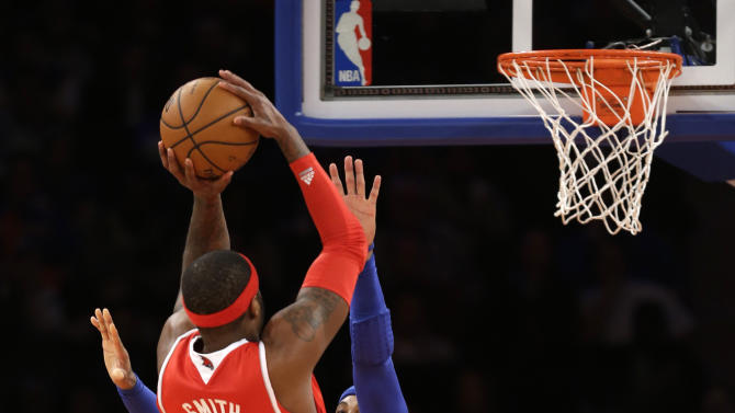 Atlanta Hawks forward Josh Smith (5) shoots over the defense of New York Knicks forward Carmelo Anthony (7) in the first half of an NBA basketball game at Madison Square Garden in New York, Sunday, Jan. 27, 2013.  (AP Photo/Kathy Willens)