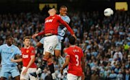 Manchester City's Belgian footballer Vincent Kompany (2nd R) scores against Manchester United during their English Premier League match at The Etihad Stadium in Manchester. City took a huge step towards the Premier League title as they beat bitter city rivals United 1-0