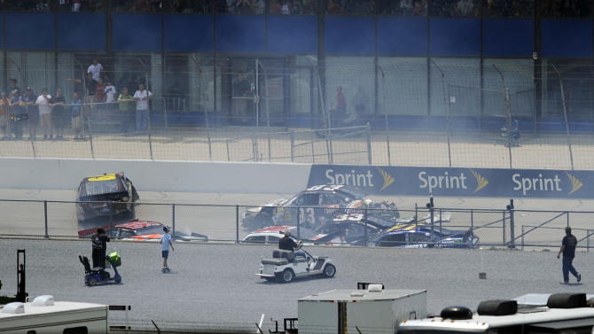 Race fans observe wreckage on the back straightaway during the NASCAR Sprint Cup Series auto race, Sunday, June 3, 2012, in Dover, Del. (AP Photo/Nick Wass)
