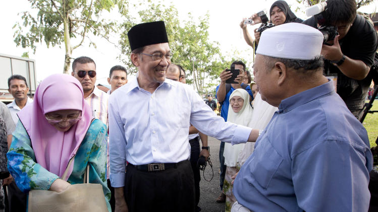 Malaysian opposition leader Anwar Ibrahim greets supporters with his wife Wan Azizah, left, after voting at Penanti in Penang state in northern Malaysia, Sunday, May 5, 2013. Malaysians have begun voting in emotionally charged national elections that could see the long-ruling coalition ousted after nearly 56 years in power. (AP Photo/Mark Baker)
