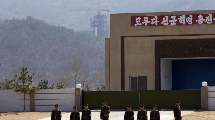 North Korean soldiers stand in front of the country's Unha-3 rocket, slated for liftoff between April 12-16, as they wait to give a security check to arriving journalists at Sohae Satellite Station in Tongchang-ri, North Korea on Sunday April 8, 2012. North Korean space officials have moved a long-range rocket into position for this week's controversial satellite launch, vowing Sunday to push ahead with their plans in defiance of international warnings against violating a ban on missile activity. (AP Photo/Ng Han Guan)