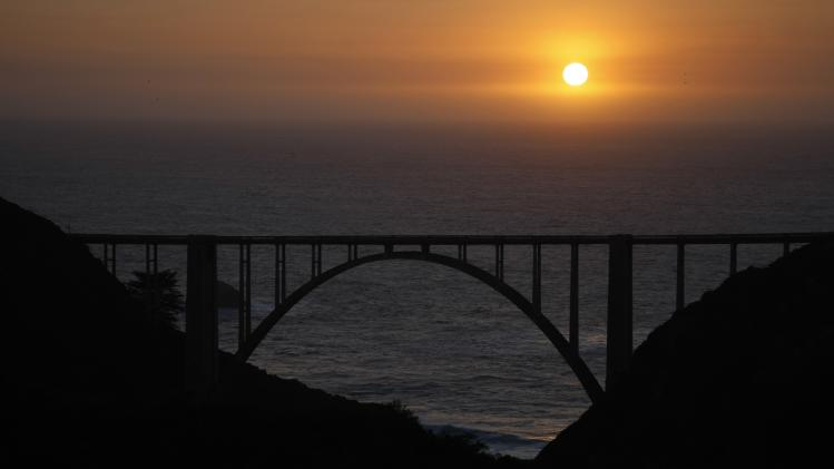 The sun sets over the Pacific Ocean behind Bixby Bridge on Highway 1 north of Big Sur