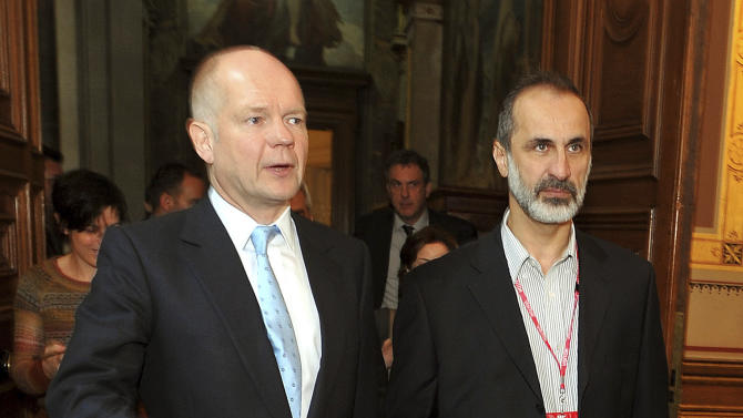 Britain's Foreign Secretary William Hague, left,  walks with  head of the new Syrian National Coalition for Opposition and Revolutionary Forces Mouaz al-Khatib to a meeting on the continuing conflict in Syria, at the Foreign and Commonwealth office in Whitehall central  Friday Nov. 16, 2012. (AP Photo/ John Stillwell/Pool)