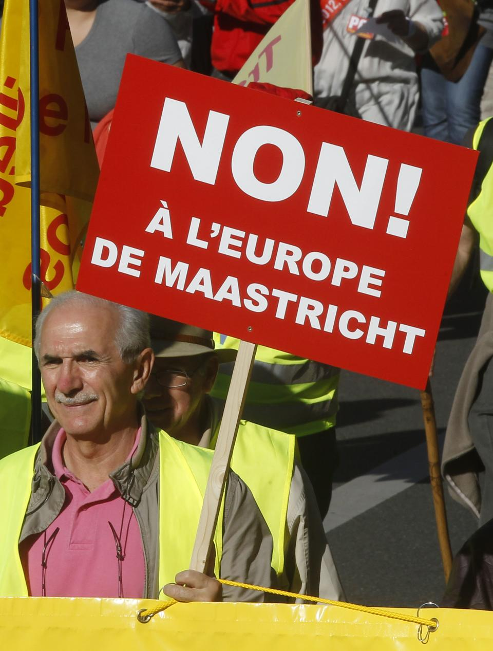 "A demonstrator holds a placard which reads,""No to the Europe of Maastrich"" to protest against the austerity measures announced by the French government, in Paris, Sunday, Sept 30, 2012. (AP Photo/Michel Euler)"