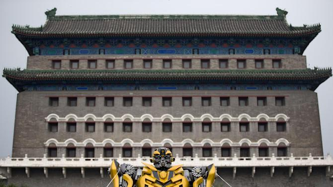 "A replica model of the Transformers character Bumblebee stands in front of Qianmen Gate, as part of a promotion of the movie ""Transformers: Age of Extinction"" in Beijing, China Saturday, June 21, 2014. A Beijing property developer said Saturday it has terminated cooperation with the new ""Transformers"" movie, wants Paramount Pictures to make edits to it and is asking China to suspend screenings of the blockbuster film. The company owns the Pangu Plaza, a dragon-shaped hotel, office and mall complex that stretches the length of half a dozen football fields and is featured in ""Transformers: Age of Extinction,"" the latest installment of the hit franchise. (AP Photo/Andy Wong)"