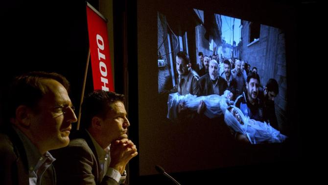 Chairman of the jury of the 2013 World Press Photo contest, Vice President and Director of Photography of The Associated Press, Santiago Lyon, left, and director of World Press Photo Michiel Munneke, right, answer questions during a press conference as the winning picture by Paul Hansen, Sweden, for Dagens Nyheter, is projected on a screen in Amsterdam, Friday Feb. 15, 2013.  (AP Photo/Peter Dejong)