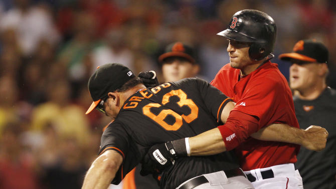 Boston Red Sox's Marco Scutaro tackles Baltimore Orioles relief pitcher Kevin Gregg (63) after Gregg got into a fight with Boston Red Sox's David Ortiz during the eighth inning of a baseball game at Fenway Park in Boston Friday, July 8, 2011. (AP Photo/Winslow Townson)