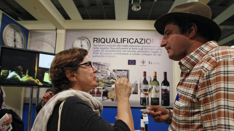 "Marcio Alexandre Alberto, a Brazilian sommelier, right, is flanked by an unidentified woman tasting a glass of white wine in a 'Pon sicurezza project' stand at the 46th edition of the annual International Wine and Spirits Exhibition ""Vinitaly"", in Verona, northern Italy, Monday, March 26, 2012. The wine exhibition runs until March 28.  (AP Photo/Luca Bruno)"