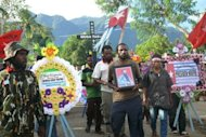 Image provided by the Papua Cooperation Forum in July shows a supporter carrying the portrait of Mako Tabuni, the slain vice chairman of the National Committee for West Papua, during his funeral in Jayapura. Canberra called on Wednesday for an Indonesian inquiry into his killing