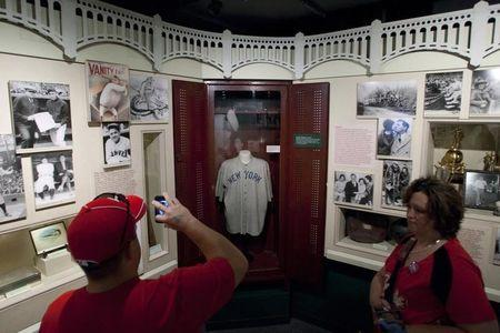 Visitors look at the jersey of baseball great Ruth displayed in a Yankee Stadium locker at the National Baseball Hall of Fame in Cooperstown, New York
