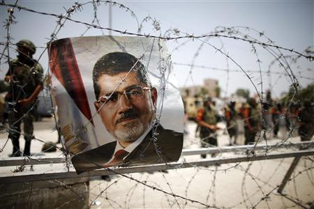 File photo of a portrait of deposed Egyptian President Mohamed Mursi seen on barbed wire outside the Republican Guard headquarters in Cairo