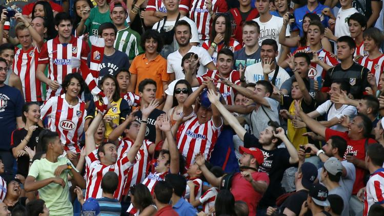 Atletico Madrid's fans in the tribune try to catch a ball thrown to them by newly signed French soccer player Antoine Griezmann during a media presentation at the Vicente Calderon stadium in Madrid
