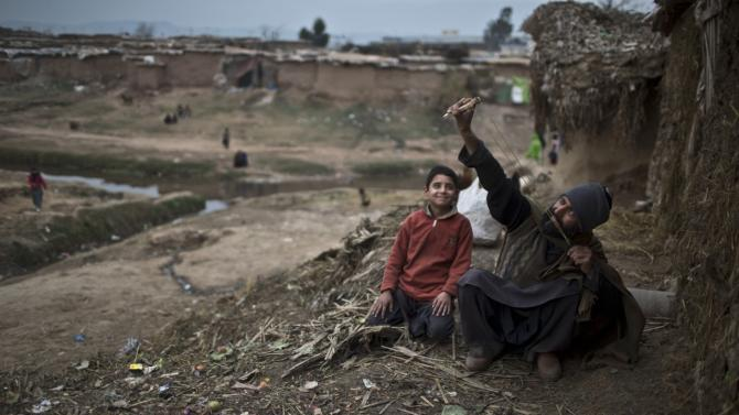 An Afghan refugee man refugee man shows his son how to use a slingshot, in a slum on the outskirts of Islamabad, Pakistan, Wednesday, Jan. 28, 2015. (AP Photo/Muhammed Muheisen)