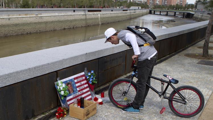 An unidentified youth looks at a memorial of candles and flowers for U.S. student Austin Bice, by the river Manzanares in Madrid Wednesday March 9, 2011. The body of San Diego State U.S. exchange student Austin Bice, was found Tuesday in the river 10 days after he went missing following a night out, a police official said. The sign says 'Murdered in Madrid, Americans demand Justice', even though a  Spanish official says forensic experts are still to carry out an autopsy but it could take weeks before the result is known. (AP Photo/Paul White)