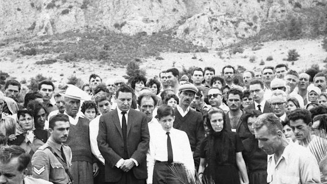 "FILE - In this Sept. 13, 1962 file photo, Mike Wallace stands before his son Peter's grave as the casket is lowered at Kamari Village, Peloponnesus, Greece, after Peter Wallace fell to his death in a accident while climbing a steep mountain in Greece. Behind Wallace is his stepson Andrew, and next to him is his son, Chris, 14, with his mother, Norma Leonard, now Mrs. Bill Leonard, and Mrs. Lorraine Wallace. Wallace, the dogged, merciless reporter and interviewer who took on politicians, celebrities and other public figures in a 60-year career highlighted by the on-air confrontations that helped make ""60 Minutes"" the most successful primetime television news program ever, has died. He was 93. (AP Photo, File)"