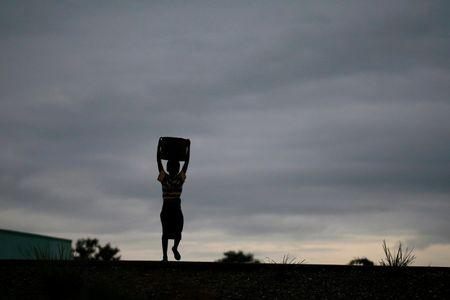 Storm clouds loom as a child carries water from a communal borehole near Malawi's capital Lilongw