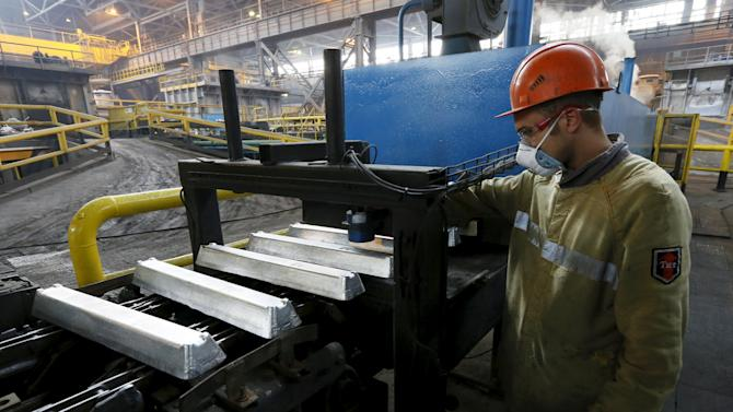 A worker watches aluminium ingots on a conveyor belt at the Rusal Sayanogorsk aluminium smelter outside the town of Sayanogorsk