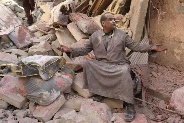 A survivor sits on rubble of collapsed buildings at a site hit by what activists said was a barrel bomb dropped by forces loyal to Syria's President Bashar al-Assad in Aleppo's al-Sakhour dist