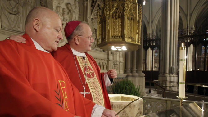 Archbishop Timothy M. Dolan, right, is joined by Msgr. Robert Ritchie, rector of St. Patrick's Cathedral, after Dolan used an iPad to light the symbolic first virtual prayer candle on the Cathedral's newly revamped website, during a ceremony in New York's St. Patrick's Cathedral, Thursday morning, June 30, 2011. The physical candle, at right, will remain in the Cathedral to represent all virtual prayer candles lit through the website. (AP Photo/Richard Drew)