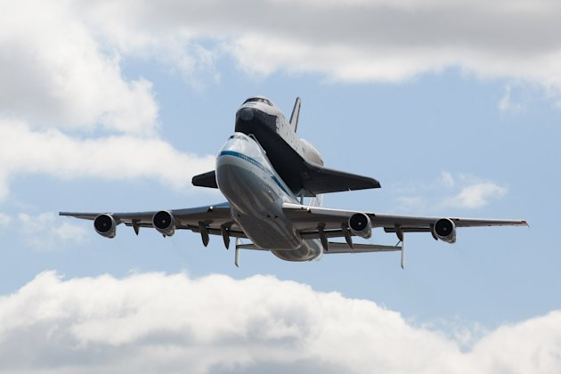 FILE - In this April 27, 2012, file photo, space shuttle Enterprise, riding on the back of the NASA 747 Shuttle Carrier Aircraft performs a fly-by above JFK International Airport,  in New York.  Enter