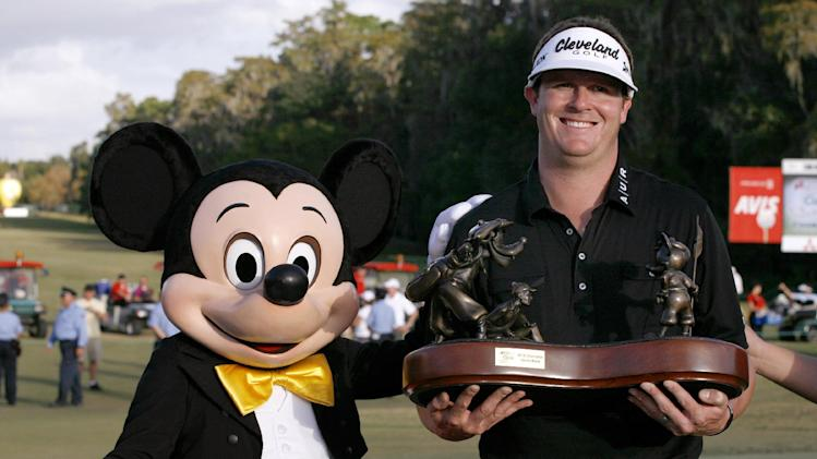 "Charlie Beljan, right, and ""Mickey Mouse"" hold up the trophy on the 18th green following the final round of the Children's Miracle Network Hospitals golf tournament in Lake Buena Vista, Fla., Sunday, Nov. 11, 2012. (AP Photo/Reinhold Matay)"