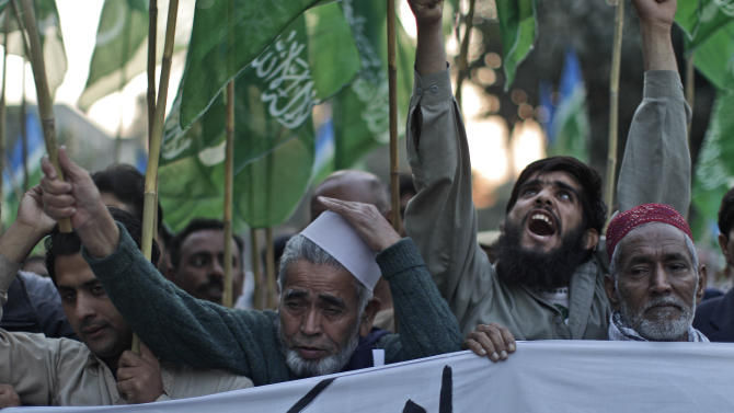 """Pakistani protestors attend a rally to condemn NATO helicopters attacks on Pakistani troops, on the outskirts of Islamabad, Pakistan, Sunday, Nov. 27, 2011. Pakistan on Saturday accused NATO helicopters and fighter jets of firing on two army checkpoints in the country's northwest and killing 24 soldiers. Islamabad retaliated by closing the border crossings used by the international coalition to supply its troops in neighboring Afghanistan. """" banner reads in English, """" American"""". (AP Photo/Muhammed Muheisen)"""