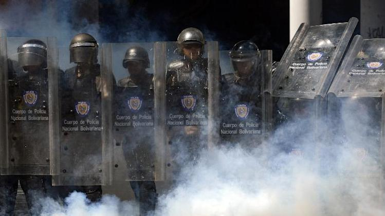 Members of the National Police look at anti-government activists during a protest against Venezuelan President Nicolas Maduro, in Caracas, on March 20, 2014