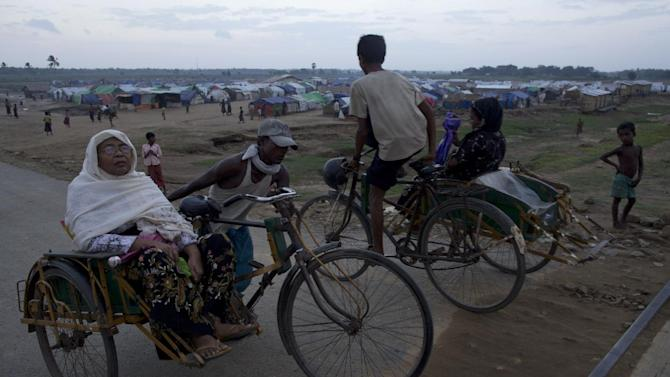 Rickshaw pullers go pass a camp for Internally displaced Rohingya people in Sittwe, northwestern Rakhine State, Myanmar, ahead of the arrival of Cyclone Mahasen, Wednesday, May 15, 2013.  The cyclone was only a day or two away, churning through the Indian Ocean and carrying with it winds and rains that authorities warn could quickly turn deadly.  But in dozens of refugee camps that spatter Myanmar's western coast, where tens of thousands of member of the displaced Rohingya people live in plastic-roofed tents and huts made of reeds, an order to evacuate ahead of the storm was met with widespread refusal.  (AP Photo/Gemunu Amarasinghe)