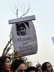 "A Pakistani activist carries a placard with a photograph of gunshot victim Malala Yousafzai as they shout ant-Taliban slogans during a protest rally in Islamabad. International outrage grew Thursday at the shooting of a teenage Pakistani campaigner by the Taliban, with US President Barack Obama leading condemnation of the ""disgusting"" attack"
