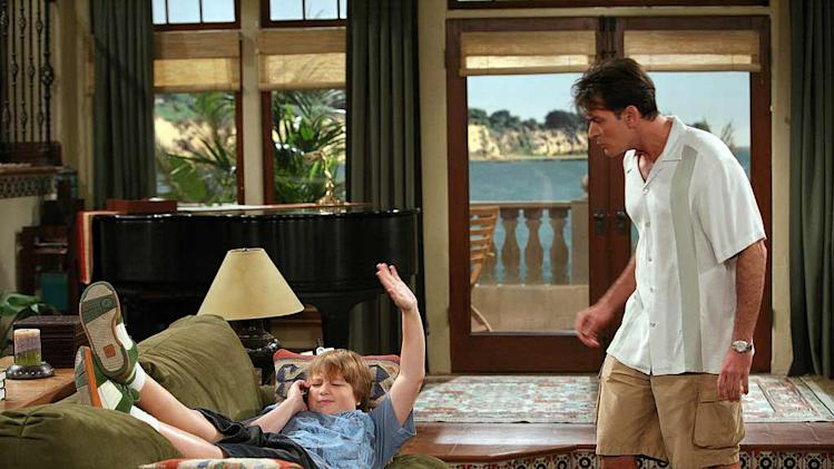 Jake (Angus T. Jones, left) tells his Uncle Charlie (Charlie Sheen, right) to stop bothering him while he is talking to his new girlfriend on the phone, on Two and a Half Men.