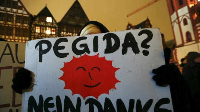 An opponent of the movement of Patriotic Europeans Against the Islamisation of the West (PEGIDA) holds a placard reading 'PEGIDA? No Thank You' during a demonstration against PEGIDA at Roemer landmark in Frankfurt