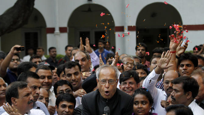 Relatives throw flower petals as India's president elect Pranab Mukherjee addresses media outside his residence after winning the election in New Delhi, India, Sunday, July 22, 2012. The candidate from India's governing Congress party, former Finance Minister Mukherjee, was declared winner Sunday in the election for the country's next president, a largely ceremonial position. (AP Photo/ Manish Swarup)