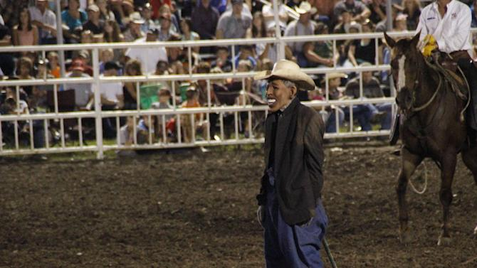 """This photo provided by Jameson Hsieh shows a clown wearing a mask intended to look like President Obama at the Missouri State Fair. The announcer asked the crowd if anyone wanted to see """"Obama run down by a bull,"""" according to a spectator. """"So then everybody screamed. ... They just went wild,"""" said Perry Beam, who attended the rodeo at the State Fair in Sedalia on Saturday Aug. 10, 2013. State Fair officials apologized calling the display inappropriate and disrespectful. (AP Photo/Jameson Hsieh)"""