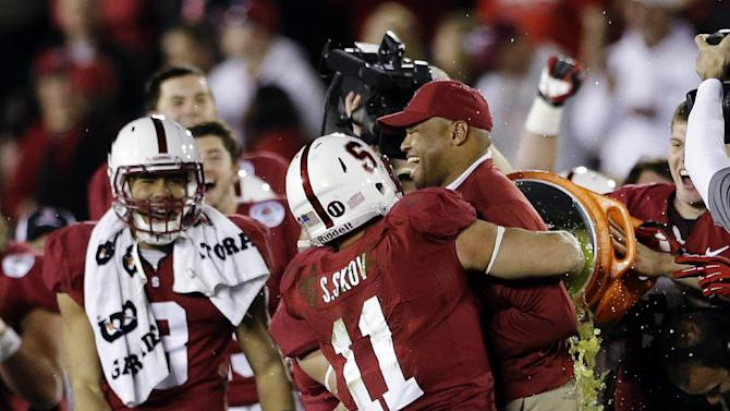Stanford head coach David Shaw is hugged by linebacker Shayne Skov (11) as he is doused following their 20-14 win over Wisconsin in the Rose Bowl NCAA college football game, Tuesday, Jan. 1, 2013, in Pasadena, Calif. (AP Photo/Lenny Ignelzi)