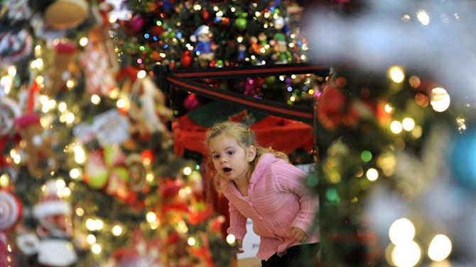 FILE - In this Sunday Nov. 25, 2012, file photo,  Carly Serepetti, checks out the decorated Christmas trees on display in Dearborn, Mich.  With a little planning, a little help and a lot of resolve, holiday entertaining doesn't have to mean you're too stressed out to enjoy your own party. (AP Photo/Detroit News, David Guralnick)