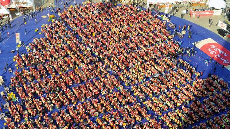 Some 3,000 South Korean volunteers make kimchi, a traditional Korean dish of spicy fermented cabbage and radish, during a mass kimchi-making event for low-income families, outside Seoul city hall, on November 13, 2013