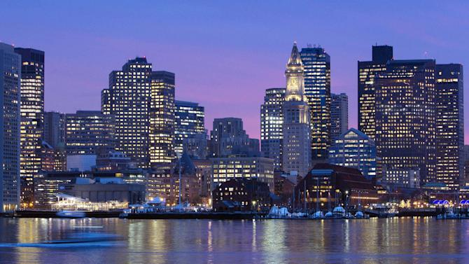 FILE - In this Jan. 6, 2012 file photo, the Boston city skyline is illuminated at dusk as it reflects off the waters of Boston Harbor. When the U.S. decided to bid for the 2024 Olympics, many experts felt an American city would be an early front-runner in the global race. Now, it's uncertain whether the bid will even make it to a final vote. International Olympic Committee members are watching with a mixture of surprise and puzzlement as Boston, reeling from a lack of public support, struggles to keep its bid afloat. (AP Photo/Michael Dwyer, File)