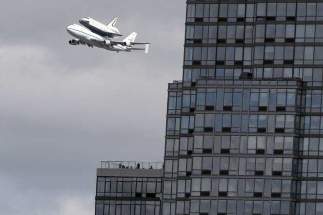 People watch from the balcony of a building as the space shuttleEnterprise, riding on the back of the NASA 747 Shuttle Carrier Aircraft, cruises over the Hudson river,  Friday, April 27, 2012 in New 